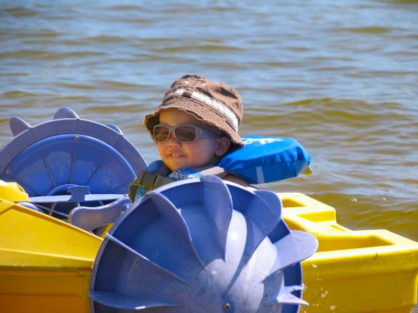 Young child riding on a paddle boat